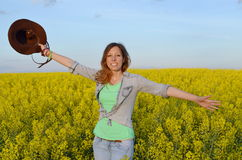Beautiful girl posing in a field of yellow flowers Stock Image