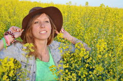 Beautiful girl posing in a field of yellow flowers Stock Photo