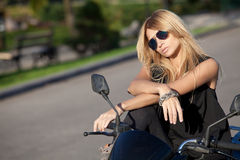 Beautiful girl posing on a motorcycle Stock Image
