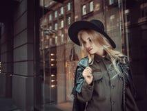Beautiful girl posing near glass wall of the shopping center. Stock Photography