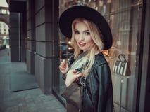 Beautiful girl posing near glass wall of the shopping center. Stock Photos