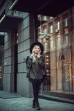 Beautiful girl posing near glass wall of the shopping center. Stock Photo