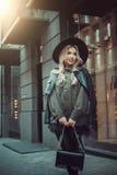 Beautiful girl posing near glass wall of the shopping center. Royalty Free Stock Photo