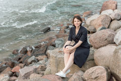 Beautiful girl posing near the sea. In a black dress Royalty Free Stock Photography