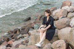 Beautiful girl posing near the sea. In a black dress Stock Photos