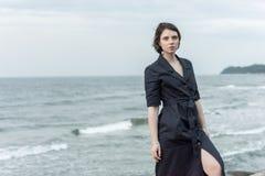Beautiful girl posing near the sea. In a black dress Stock Photography