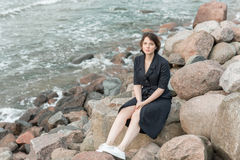 Beautiful girl posing near the sea. In a black dress Royalty Free Stock Images
