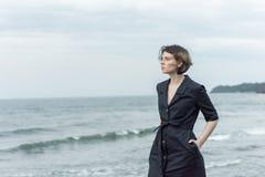 Beautiful girl posing near the sea. In a black dress Stock Image