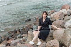 Beautiful girl posing near the sea. In a black dress Royalty Free Stock Image