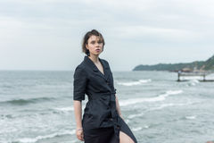 Beautiful girl posing near the sea. In a black dress Stock Images