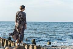 Beautiful girl posing near the sea. Beautiful girl posing in a dress near the sea Royalty Free Stock Photos