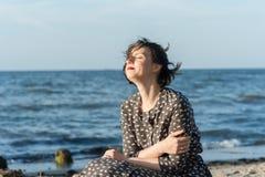 Beautiful girl posing near the sea. Beautiful girl posing in a dress near the sea Stock Image