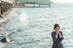Beautiful girl posing near the sea. Beautiful girl posing in a dress near the sea Stock Images