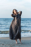 Beautiful girl posing near the sea. Beautiful girl posing in a dress near the sea Stock Photo
