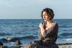 Beautiful girl posing near the sea. Beautiful girl posing in a dress near the sea Royalty Free Stock Photography