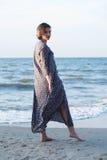 Beautiful girl posing near the sea. Beautiful girl posing in a dress near the sea Royalty Free Stock Images
