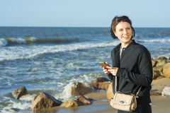 Beautiful girl posing near the sea. With a phone Royalty Free Stock Photography