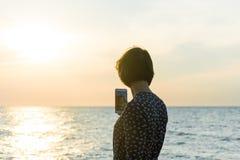 Beautiful girl posing near the sea. With a phone Stock Photos