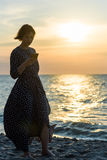 Beautiful girl posing near the sea. With a phone Royalty Free Stock Photo
