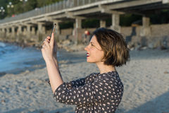 Beautiful girl posing near the sea. With a phone Royalty Free Stock Photos