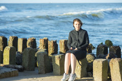 Beautiful girl posing near the sea. On stones Stock Photos