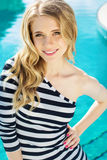 Beautiful girl posing near the swimming pool Stock Photography