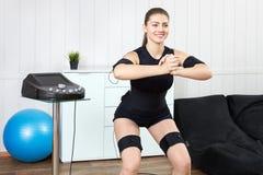 Beautiful girl posing next to muscle stimulation machine prepari. Beautiful young girl doing exercises on the machine for muscle stimulation. Innovative Stock Photography