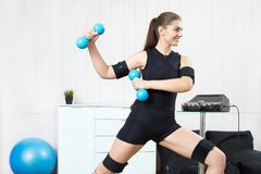 Beautiful girl posing next to muscle stimulation machine prepari. Beautiful young girl doing exercises on the machine for muscle stimulation. Innovative Stock Image