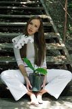Beautiful girl posing with orchid flower Stock Photo
