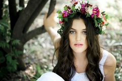 Beautiful girl posing on photo shoot in the forest. In a white dress with a floral wreath on his head royalty free stock photo