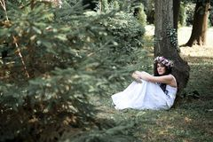 Beautiful girl posing on photo shoot in the forest. In a white dress with a floral wreath on his head royalty free stock image
