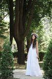 Beautiful girl posing on photo shoot in the forest. In a white dress with a floral wreath on his head stock images