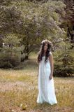 Beautiful girl posing on photo shoot in the forest. In a white dress with a floral wreath on his head royalty free stock photos