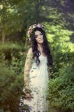 Beautiful girl posing on photo shoot in the forest. In a white dress with a floral wreath on his head royalty free stock photography