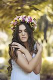 Beautiful girl posing on photo shoot in the forest. In a white dress with a floral wreath on his head stock photos