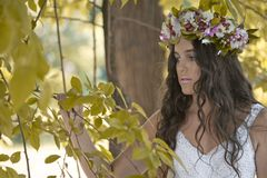Beautiful girl posing on photo shoot in the forest. In a white dress with a floral wreath on his head stock image
