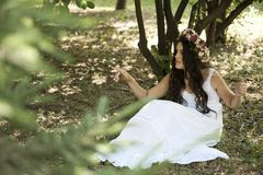 Beautiful girl posing on photo shoot in the forest. In a white dress with a floral wreath on his head stock photo