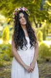 Beautiful girl posing on photo shoot in the forest. In a white dress with a floral wreath on his head royalty free stock images