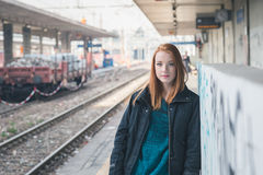 Beautiful girl posing in a railroad station Royalty Free Stock Images