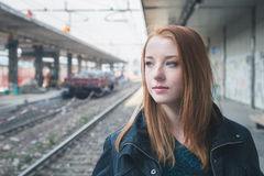 Beautiful girl posing in a railroad station Royalty Free Stock Photos