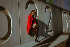 Beautiful girl posing with red coat Stock Image