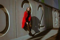 Beautiful girl posing with red coat. Beautiful girl posing in the street with red coat Stock Photos