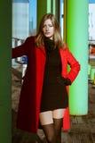 Beautiful girl posing with red coat. Beautiful girl posing in the street with red coat Stock Photo