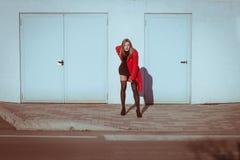 Beautiful girl posing with red coat. Beautiful girl posing in the street with red coat Royalty Free Stock Photos