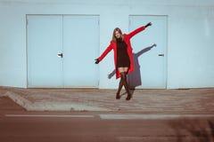 Beautiful girl posing with red coat. Beautiful girl posing in the street with red coat Royalty Free Stock Photography