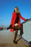 Beautiful girl posing with red coat. Beautiful girl posing in the street with red coat Stock Images