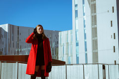 Beautiful girl posing with red coat. Beautiful girl posing in the street with red coat Stock Photography