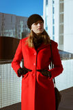 Beautiful girl posing with red coat. Beautiful girl posing in the street with red coat Stock Image