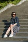 Beautiful girl posing  on the steps. Beautiful girl posing in a jeans jacket on the steps Stock Images