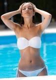 Beautiful girl posing in the swimming pool. Stock Images